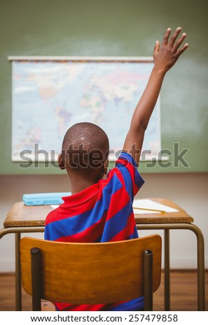 Rear view of little boy raising hand in the classroom - stock photo