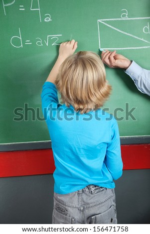 Rear view of little boy writing formula on greenboard in classroom - stock photo