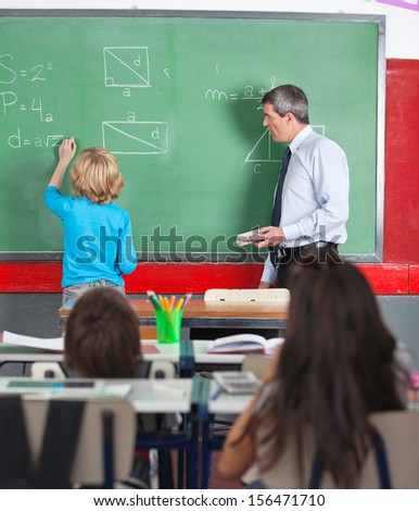 Rear view of little boy writing on board while teacher looking at him in classroom - stock photo