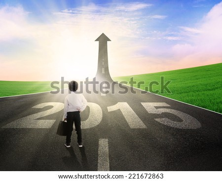 Rear view of little business person standing on the road to future 2015