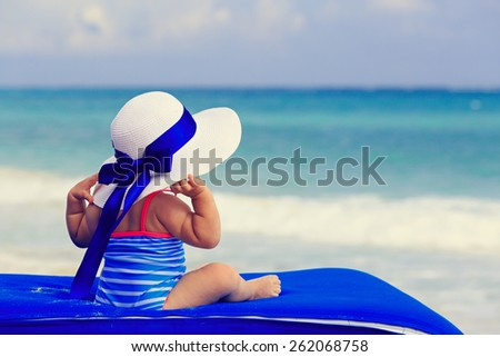 rear view of little girl in big hat on summer tropical beach - stock photo