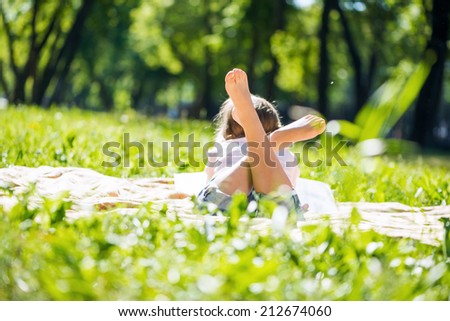 Rear view of little girl lying in summer park