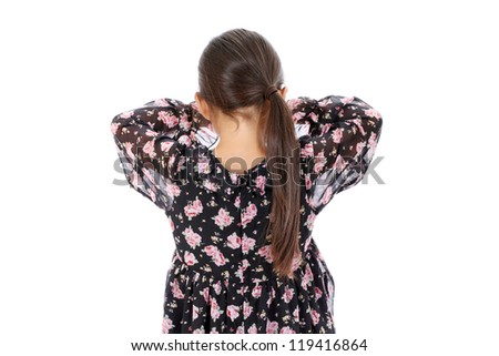 Rear view of little girl playing hide-and-seek hiding face - stock photo