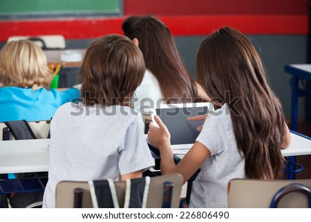 Rear view of little schoolgirl using digital tablet with boy at desk in classroom - stock photo