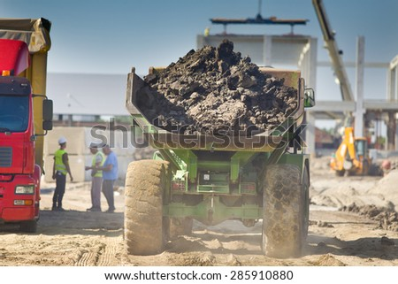Rear view of loaded truck carrying out soil from construction site - stock photo