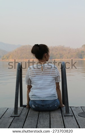Rear view of lonely woman sitting on floating house resort. - stock photo