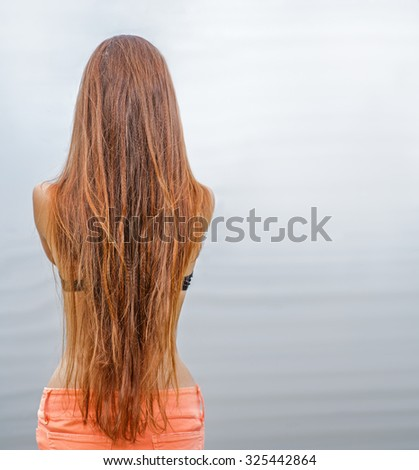 Rear view of long haired redhead woman posing against sea water, a lot of space for text - stock photo