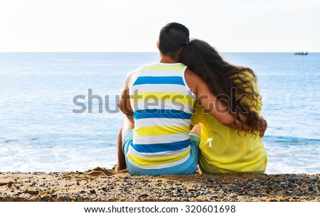 Rear view of loving couple having romantic date on sandy beach  - stock photo