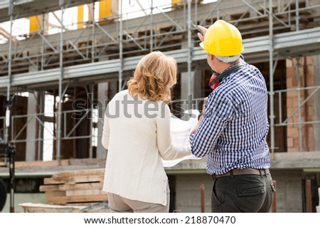 Rear View Of Male Architect And Client Looking At Under Construction Building - stock photo