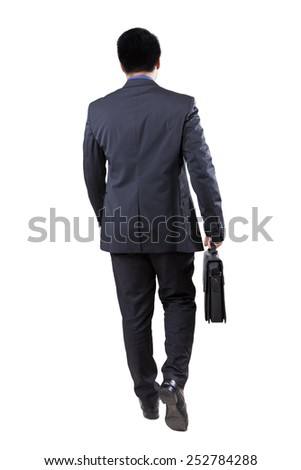 Rear view of male businessperson walking in the studio while carrying briefcase - stock photo