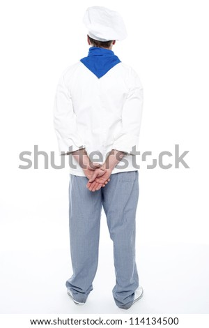 Rear view of male chef posing with hands behind isolated over white - stock photo