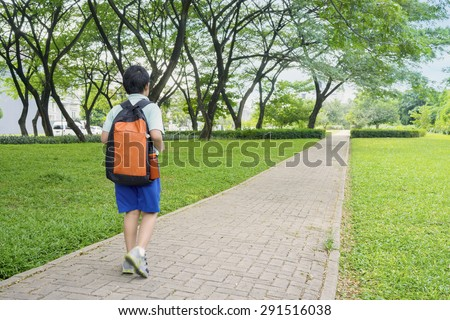 Rear view of male elementary school student walking alone to school while carrying backpack - stock photo