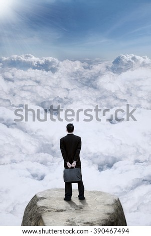 Rear view of male entrepreneur holding suitcase while standing on the mountain peak and looking at clouds - stock photo
