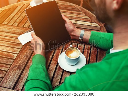 Rear view of male freelancer holding digital tablet with empty screen, man sitting at the table with cup of coffee while using touch screen tablet with blank screen, student working on tablet pc,flare - stock photo