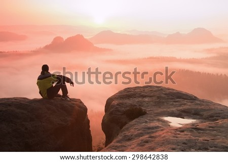 Rear view of male hiker sitting on the rocky peak  while enjoying a daybreak above mountains valley