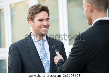 Rear view of male journalist taking interview of happy businessman outdoors