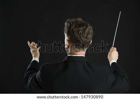 Rear view of male music conductor directing with his baton against black background - stock photo