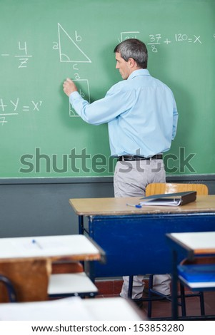 Rear view of male professor solving mathematics on greenboard in classroom - stock photo