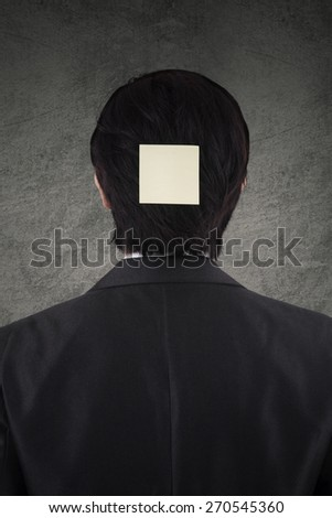Rear view of male worker attaching empty post it on his head - stock photo
