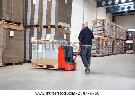 Rear view of male worker pushing handtruck loaded with goods at distribution warehouse - stock photo