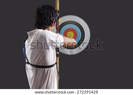 Rear view of man aiming target with bow against black background Rear view of man aiming target with bow against black background - stock photo
