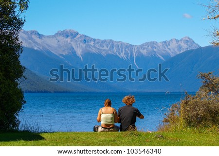 Rear view of man and woman couple sitting by a blue lake with mountain. Concept shot for love, romance or loss.