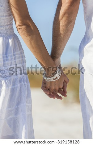 Rear view of man and woman romantic couple in white clothes holding hands on a deserted tropical beach with bright clear blue sky - stock photo