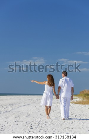 Rear view of man and woman romantic couple in white clothes walking holding hands and pointing on a deserted tropical beach with bright clear blue sky