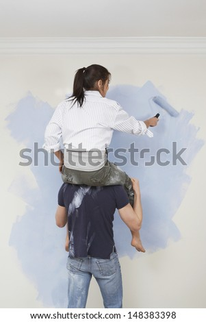 Rear view of man carries woman on his shoulders while painting at home - stock photo