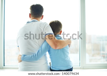 Rear view of man embracing his son - stock photo