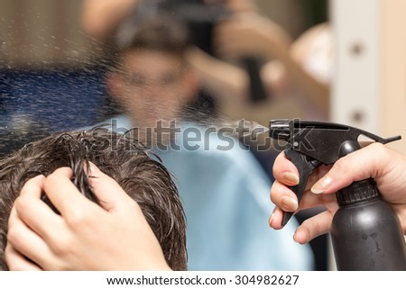 Rear view of man getting a haircut in beauty salon