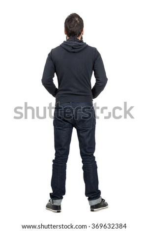 Rear view of man in black hooded shirt with rolled up jeans. Full body length portrait isolated over white studio background.  - stock photo