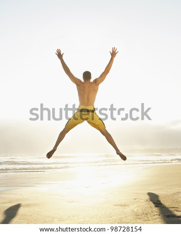 Rear view of man jumping on beach with arms raised above head
