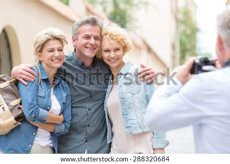 Rear view of man photographing male and female friends in city - stock photo