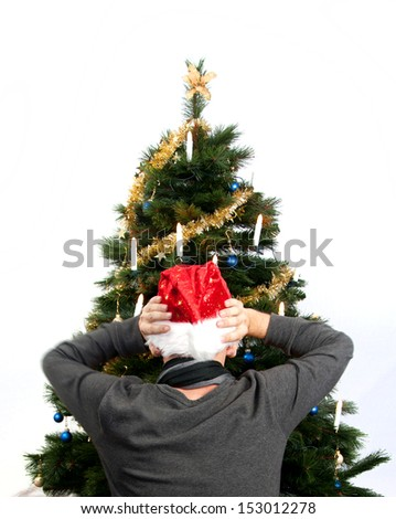 Rear view of Man sitting in front of christmas tree wearing a red christmas hat and throwing his hands up in horror - stock photo