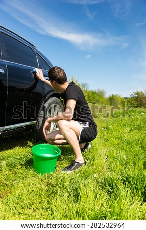Rear View of Man Washing Car with Soapy Sponge, Crouching Next to Green Bucket in Green Grassy Field on Bright Sunny Day with Blue Sky