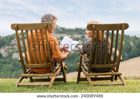 Rear View Of Mature Couple Sitting On Lounge Chair Reading Book - stock photo