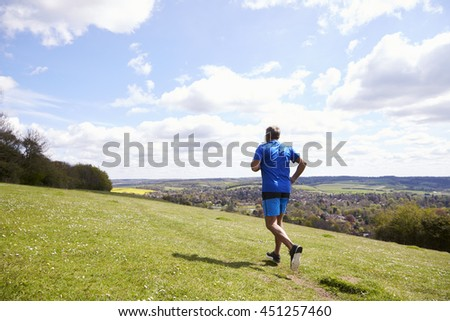 Rear View Of Mature Man Jogging In Countryside