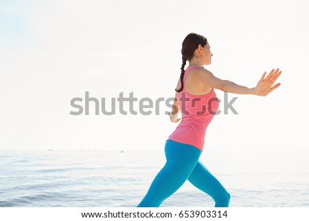 Rear view of mature woman exercising, stretching her body and arms up against sunny sky with sea background, healthy sport and fitness outdoors. Active woman working out, wellness training lifestyle.
