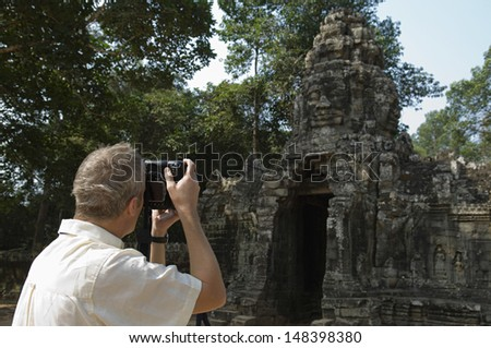 Rear view of middle aged man photographing ancient temple