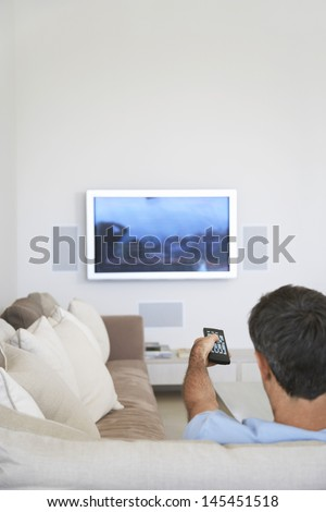 Rear view of middle aged man watching television in living room - stock photo