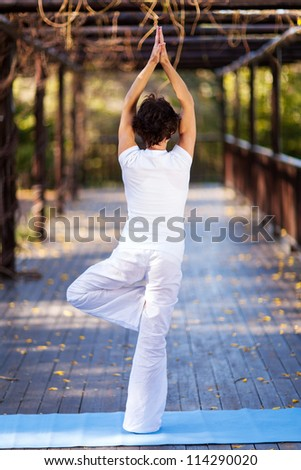 rear view of middle aged woman doing yoga pose - stock photo