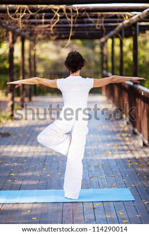 rear view of middle aged woman yoga pose - stock photo