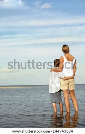 Rear view of mother and son enjoying the sea view - stock photo