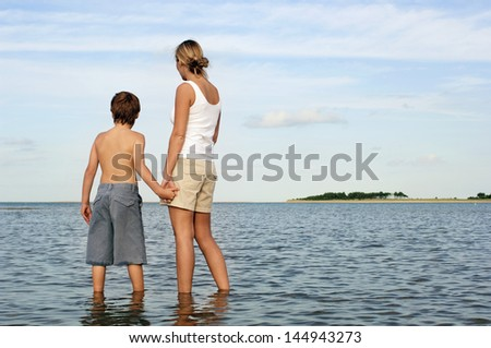 Rear view of mother and son holding hands while enjoying the sea view
