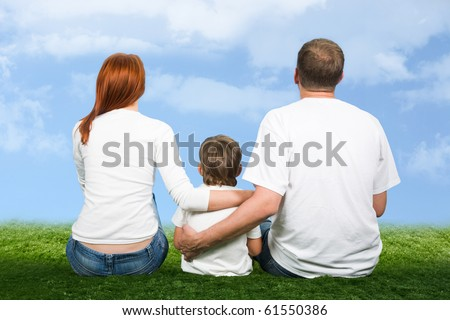 Rear view of mother, father and son sitting together - stock photo