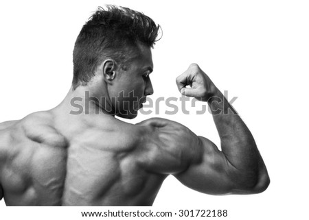 Rear view of muscular man flexing biceps. Black and white studio shot isolated on white. - stock photo