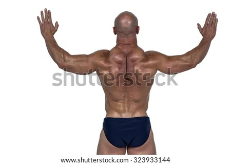 Rear view of muscular man with arms raised against white background - stock photo