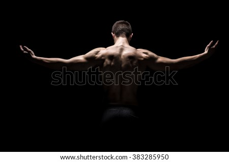 Rear view of muscular man with his arms stretched out - stock photo