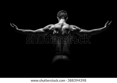 Rear view of muscular man with his arms stretched out